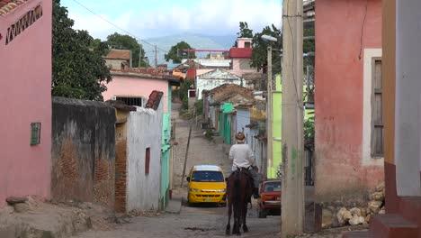 Eine-Schöne-Aufnahme-Der-Gebäude-Und-Kopfsteinpflasterstraßen-Von-Trinidad-Kuba-Mit-Vorbeifahrenden-Cowboys