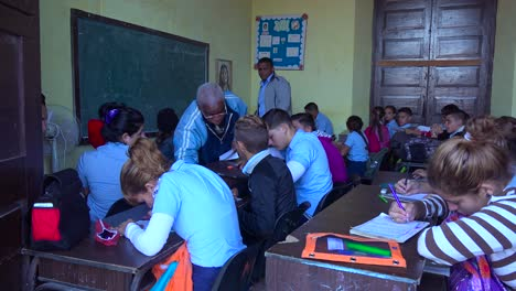 Students-study-in-a-classroom-in-Cuba-as-a-teacher-looks-on