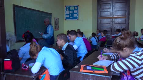 Students-study-in-a-classroom-in-Cuba-as-a-teacher-looks-on-1