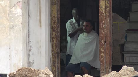 A-customer-gets-a-haircut-along-a-primitive-street-in-Havana-Cuba