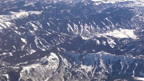 Aerial-shot-over-the-Rocky-Mountains-in-snow-in-winter