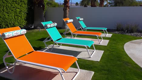 Colorful-lawn-chairs-sit-around-a-pool-at-a-Palm-Springs-home