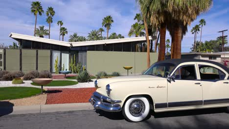 Exterior-establishing-shot-of-a-Palm-Springs-California-mid-century-modern-home-with-classic-retro-cars-parked-outside