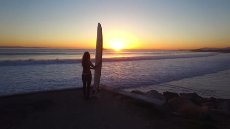An-aerial-over-a-woman-standing-with-a-surf-board-looking-out-at-the-sunset-4