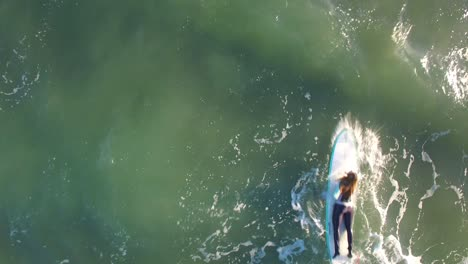 An-aerial-directly-above-a-woman-paddling-her-surfboard-through-the-waves