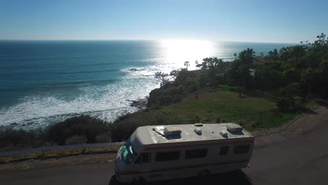 Aerial-over-a-motorhome-traveling-along-a-California-road-near-the-ocean