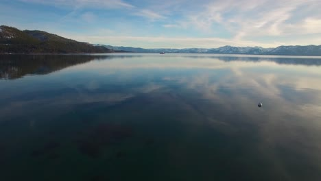 A-beautiful-aerial-shot-over-Lake-Tahoe-in-winter-with-a-paddlewheel-steamboat-in-distance