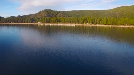 An-aerial-shot-over-Lake-Tahoe-approaching-the-shore-and-over-old-pilings-in-water