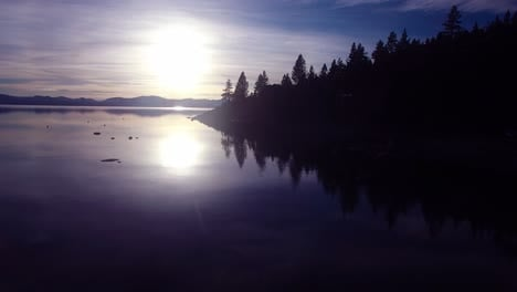 A-beautiful-aerial-shot-over-Lake-Tahoe-with-the-shoreline-in-silhouette