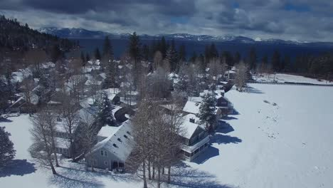 An-aerial-over-a-snow-covered-village-in-the-Sierra-Nevada-mountains-with-Lake-Tahoe-ion-the-background