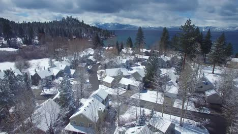 An-aerial-over-a-snow-covered-village-in-the-Sierra-Nevada-mountains-with-Lake-Tahoe-ion-the-background-1