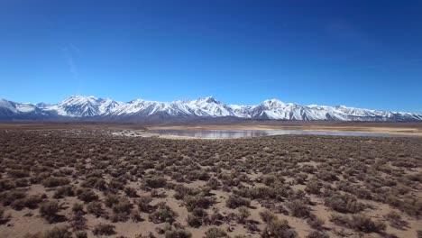 Una-Antena-Sobre-Una-Llanura-Geotérmica-En-Las-Montañas-De-Sierra-Nevada-Cerca-De-Mamut-California-Revela-Un-Lago-De-Montaña