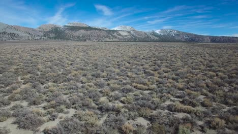 Beautiful-aerial-shot-over-desert-sagebrush-reveals-the-Mono-volcano-cones-in-the-Eastern-Sierra-Nevada-mountains-1