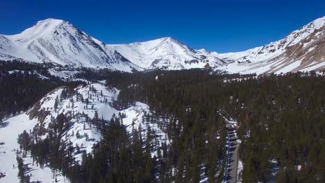 Una-Antena-Sobre-Una-Carretera-Remota-A-Través-De-Las-Nevadas-Montañas-De-Sierra-Nevada-En-Invierno