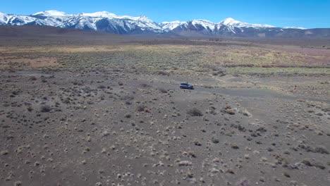 Antena-Encima-De-Un-4wd-Viajando-Por-Un-Camino-De-Tierra-En-El-Desierto-De-Mojave-Con-Las-Montañas-De-Sierra-Nevada-Distantes