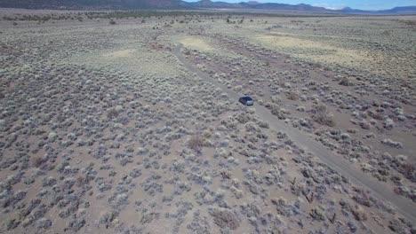 Antena-Encima-De-Un-4wd-Viajando-Por-Un-Camino-De-Tierra-En-El-Desierto-De-Mojave-Con-Las-Montañas-De-Sierra-Nevada-Distantes-2