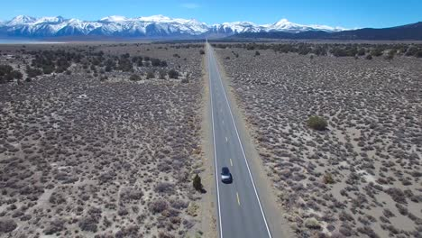 Aerial-above-a-4WD-traveling-on-a-paved-road-in-the-Mojave-Desert-with-the-Sierra-Nevada-mountains-distant