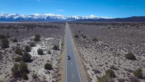 Antena-Encima-De-Un-4wd-Viajando-Por-Una-Carretera-Asfaltada-En-El-Desierto-De-Mojave-Con-Las-Montañas-De-Sierra-Nevada-Distantes-1