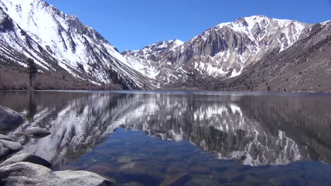 An-alpine-mountain-lake-reflects-sierra-nevada-snow-in-winter-