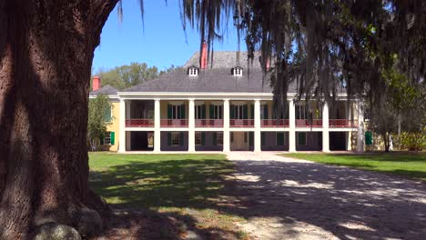 A-wide-shot-of-a-beautiful-gracious-Southern-mansion-on-an-estate-amongst-oak-trees-1