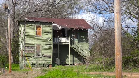 A-decaying-old-tenement-house-sits-in-a-field-in-Jackson-Mississippi