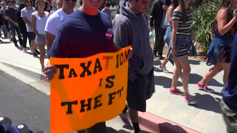 A-person-at-a-political-rally-holds-up-a-sign-saying-taxation-is-theft