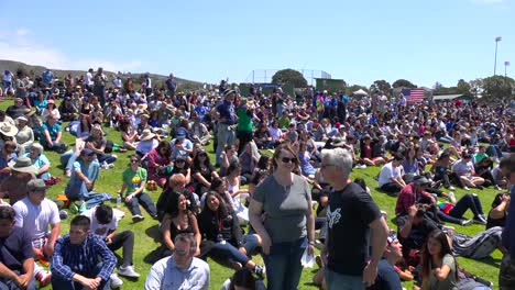 Attendees-at-a-Bernie-Sanders-rally-sit-on-a-hillside