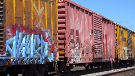 Colorful-graffiti-is-seen-on-parked-railway-boxcars