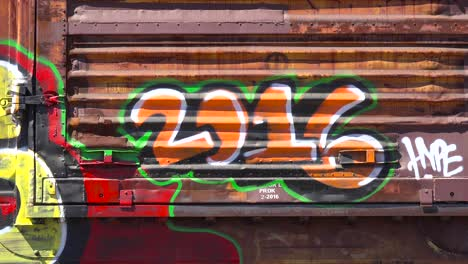 Colorful-graffiti-indicating-the-year-2016-is-seen-on-parked-railway-boxcars