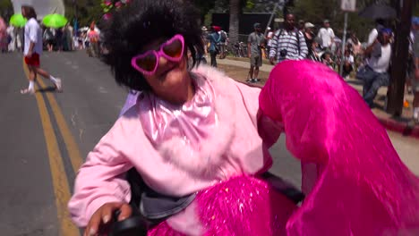 A-woman-dressed-in-pink-rocks-out-in-a-wheelchair-during-the-summer-solstice-parade-in-Santa-Barbara-California