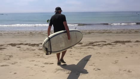 A-middle-aged-surfer-dude-carries-his-board-down-the-beach-and-into-the-water-in-Southern-California