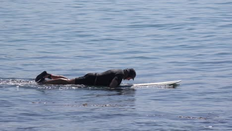 A-middle-aged-surfer-dude-paddles-his-board-in-the-waves-on-a-Southern-California-beach