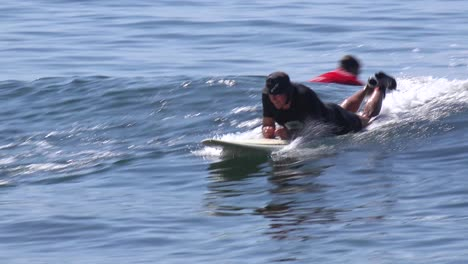 A-middle-aged-surfer-dude-bodyboards-a-wave-on-a-Southern-California-beach