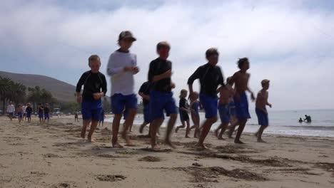 Los-Niños-Corren-A-Lo-Largo-De-La-Playa-En-Un-Campamento-Diurno-En-La-Playa-De-Santa-Bárbara-California