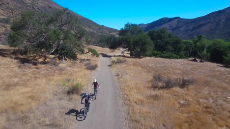 Good-aerial-following-two-mountain-bikers-riding-in-the-California-mountains-1