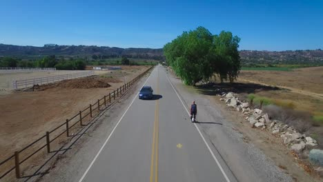 Aerial-footage-following-a-man-riding-an-electric-unicycle-down-a-road-in-California