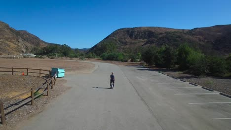 Aerial-footage-following-a-man-riding-an-electric-unicycle-down-a-road-in-California-3