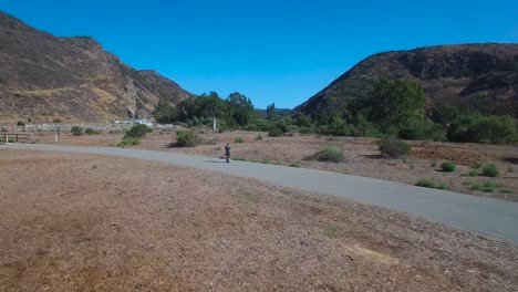 Aerial-footage-following-a-man-riding-an-electric-unicycle-down-a-road-in-California-4