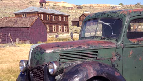 Old-green-pickup-truck-with-old-schoolhouse-background-in-the-abandoned-ghost-town-of-Bodie-California