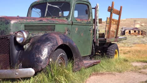 Old-green-pickup-truck-with-abandoned-house-background-in-the-ghost-town-of-Bodie-California