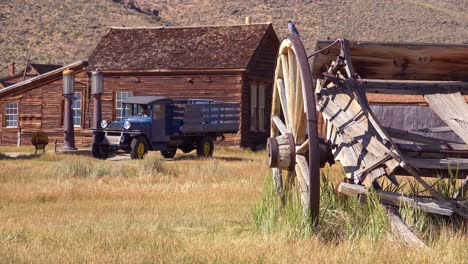 Old-green-pickup-truck-and-wagon-with-abandoned-house-background-in-the-ghost-town-of-Bodie-California