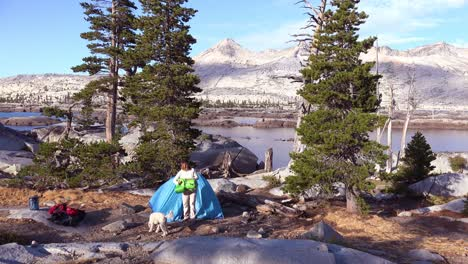 A-woman-and-her-dog-set-up-a-tent-in-the-Desolation-Wilderness-of-the-Sierra-Nevada-mountains