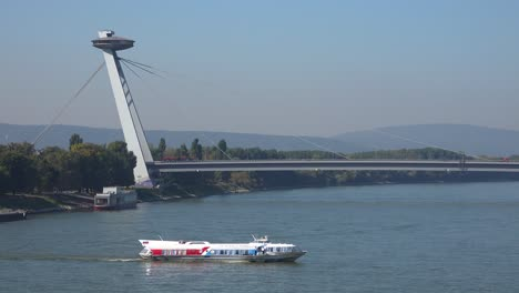 A-ferry-boat-maneuvers-on-the-Danube-River-with-the-modern-bridge-at-Bratislava-Slovakia-background