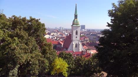 Beautiful-establishing-shot-of-downtown-Bratislava-Slovakia-with-church-foreground