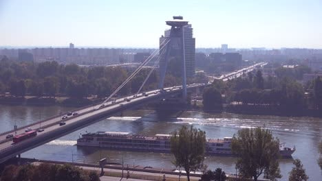 A-ferry-boat-maneuvers-on-the-Danube-River-with-the-modern-bridge-at-Bratislava-Slovakia-background-1