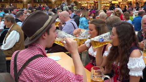 People-toast-with-large-beer-mugs-at-Oktoberfest-in-Germany