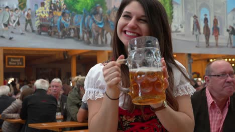 A-pretty-girl-drinks-a-large-mug-of-beer-at-Oktoberfest-Germany