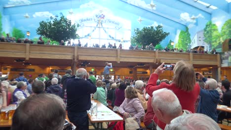 A-man-stands-on-a-table-and-downs-a-glass-of-beer-at-Oktoberfest-Germany