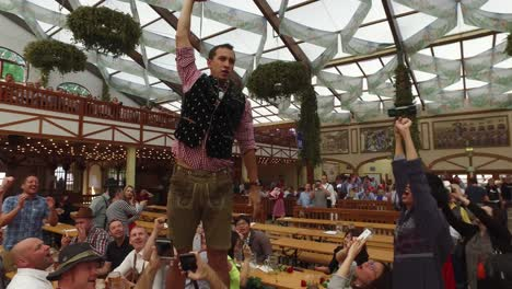 A-man-stands-on-a-table-and-downs-a-glass-of-beer-at-Oktoberfest-Germany-1