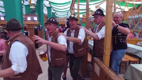 Drunken-men-celebrate-and-dance-in-a-beer-hall-during-Oktoberfest-in-Germany